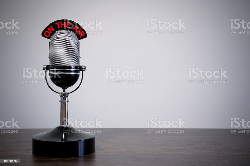 Retro desk microphone with red wording and gray background stock photo