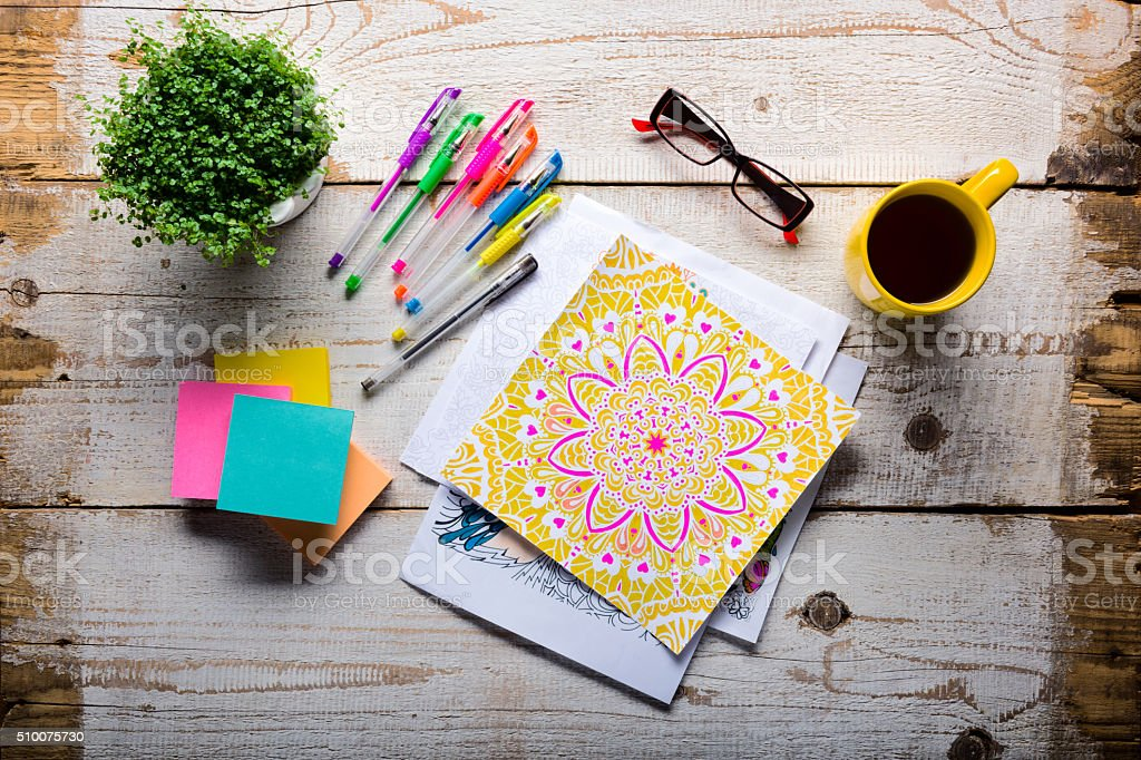Retro desk with adult coloring books, stress relieving trend stock photo