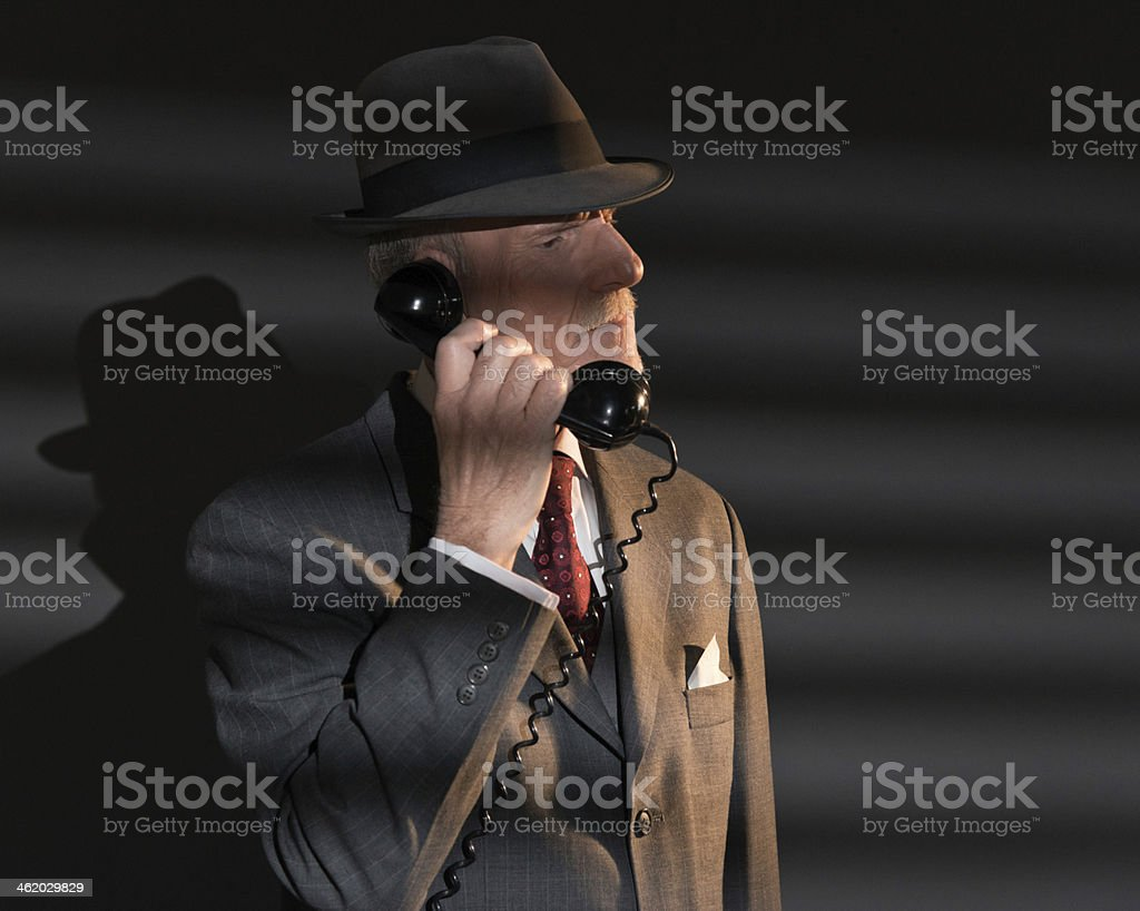 Retro detective man calling with vintage telephone at night. stock photo