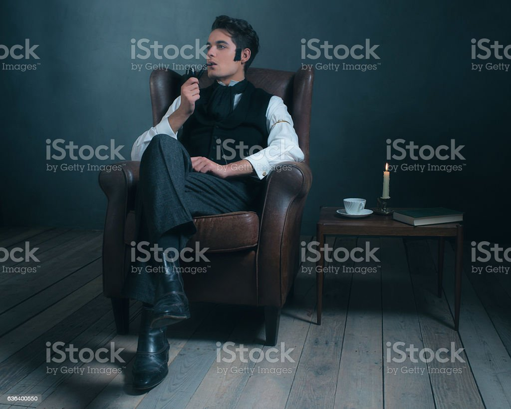 Retro dickens style man smoking pipe. Sitting in leather chair. stock photo