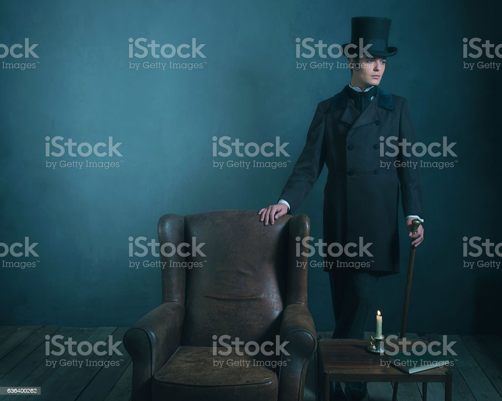 Retro dickens style man standing with cane next to chair. stock photo