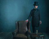 Retro dickens style man standing with cane next to chair.