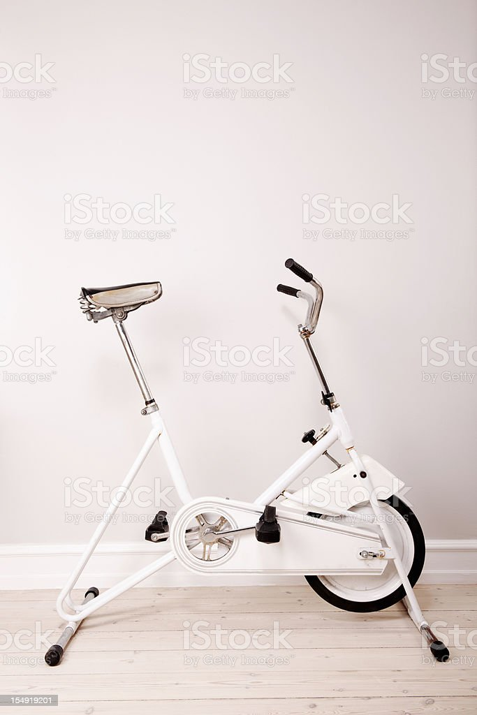 Retro Exercise Bike Against a Neutral Coloured  Wall stock photo