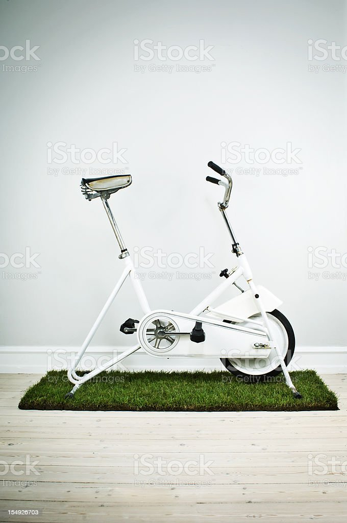 Retro Exercise Bike On Mat Made From Grass Neutral Background stock photo