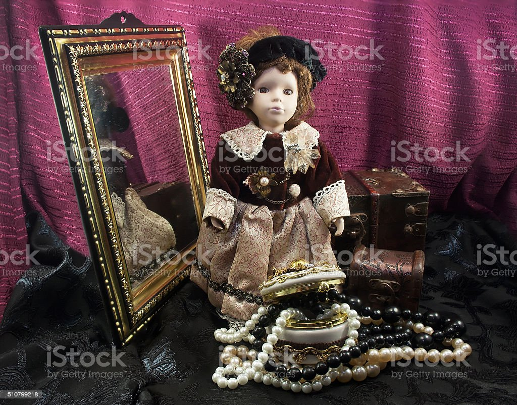 Retro fashioned porcelain doll with jewelry box. stock photo