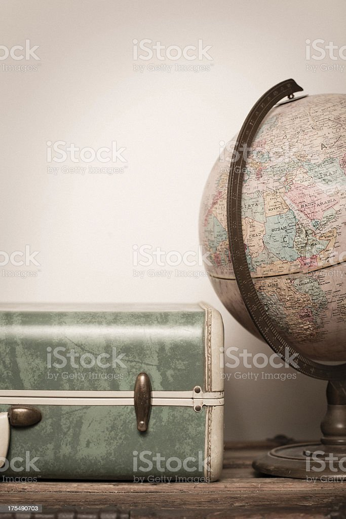 Retro Green Suitcase and Globe Sitting on Wood royalty-free stock photo