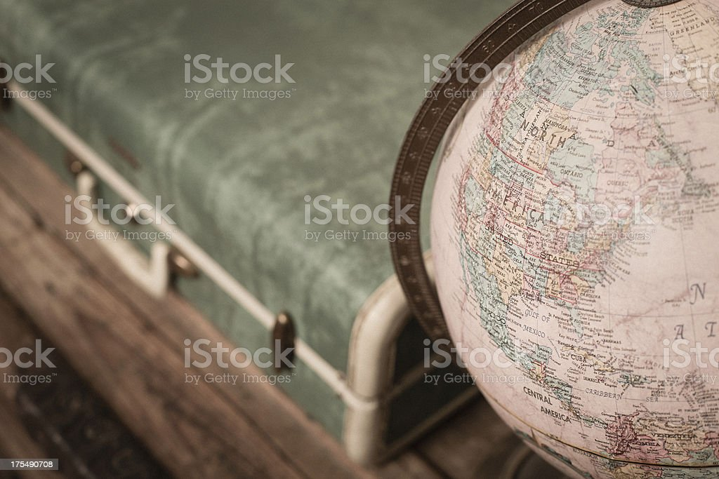 Retro Green Suitcase and Globe Sitting on Wood Trunk royalty-free stock photo