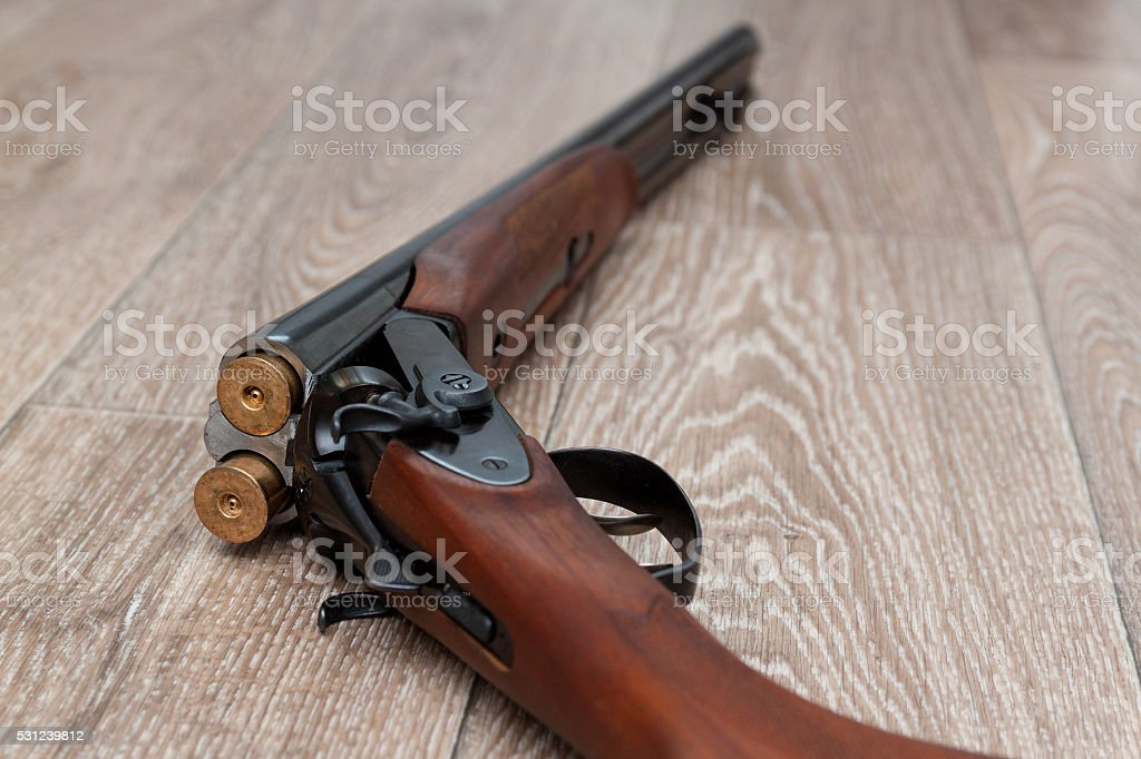 retro gun with shotgun shells on wooden stock photo