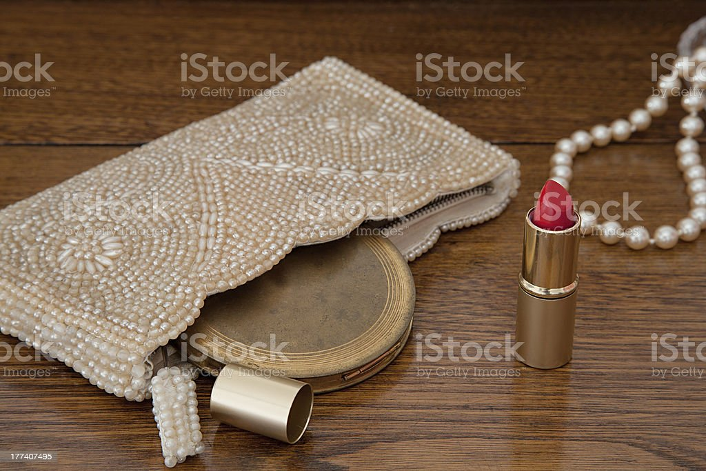 Retro Handbag, Compact, Pearls, and Red Lipstick on Dressing Table stock photo