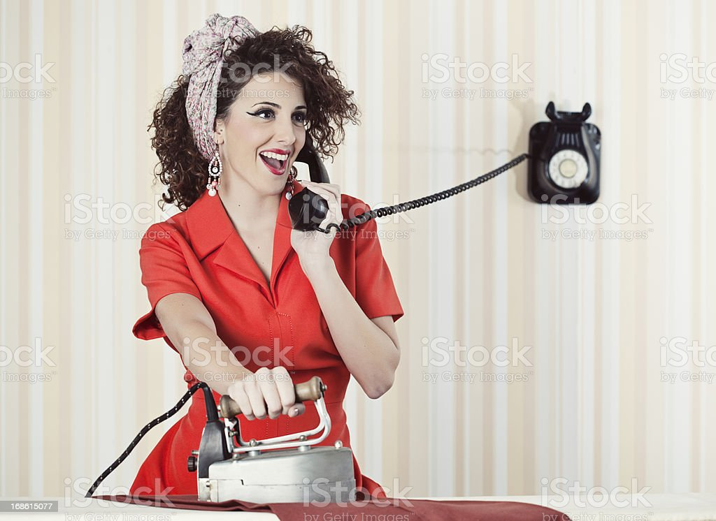 Retro house wife talking to the phone while ironing. royalty-free stock photo