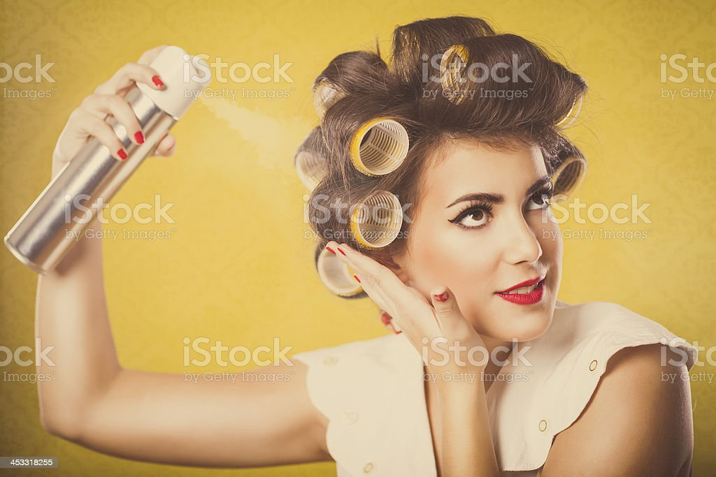 Retro housewife applying spray on her hair stock photo