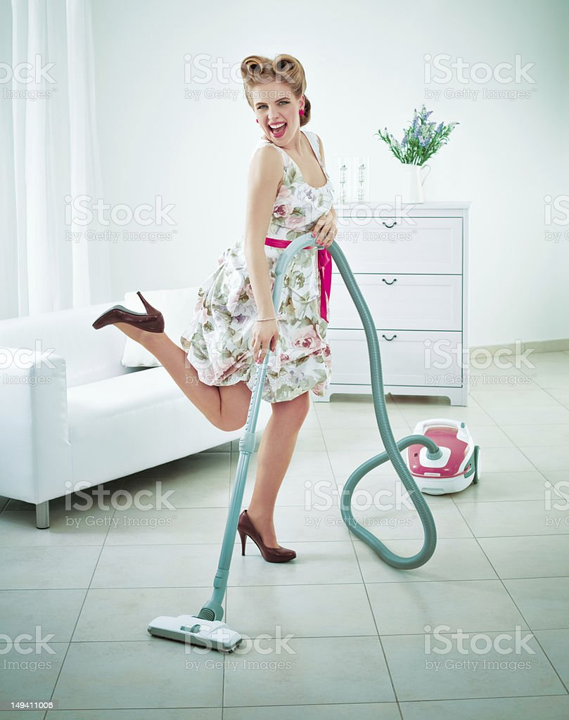 Retro housewife vacuuming a floor stock photo