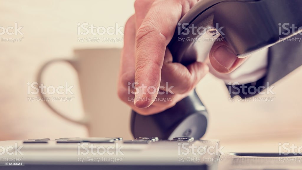 Retro image of male hand dialing a telephone number stock photo
