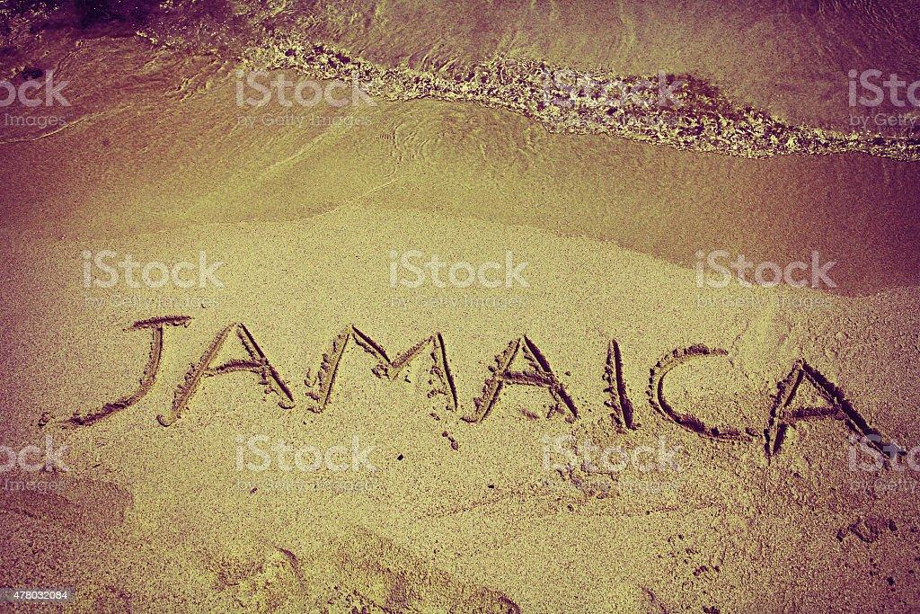 retro inscription Jamaica on beach sand stock photo