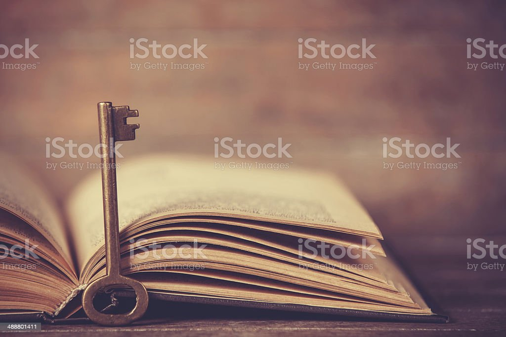 Retro key and opened book stock photo