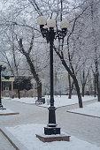 Retro lantern on a snowy city boulevard. Urban