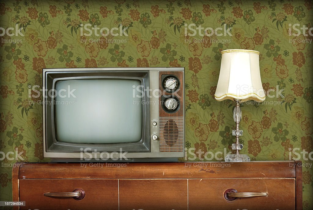 Retro living room with a TV and a lamp atop a wooden desk stock photo