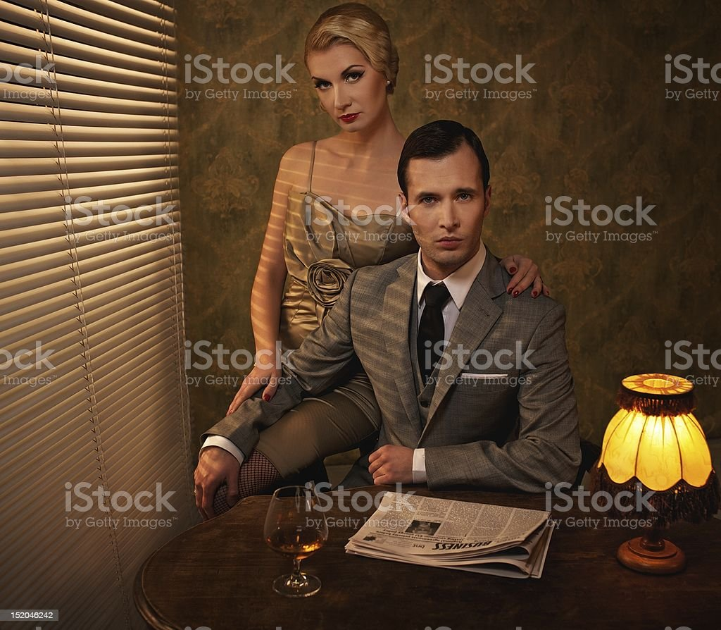 A retro man and woman couple sitting behind a table royalty-free stock photo