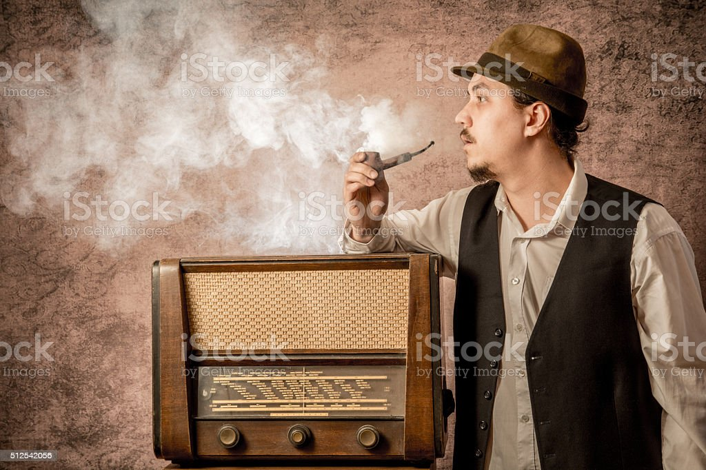 retro man smoke a pipe next to the radio stock photo