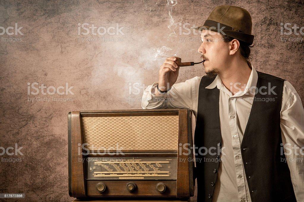 retro man smoke a pipe next to the radio stock photo