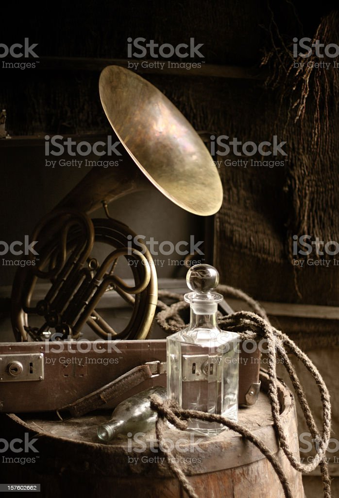 Retro music still life with French horn, suitcase and decanter royalty-free stock photo