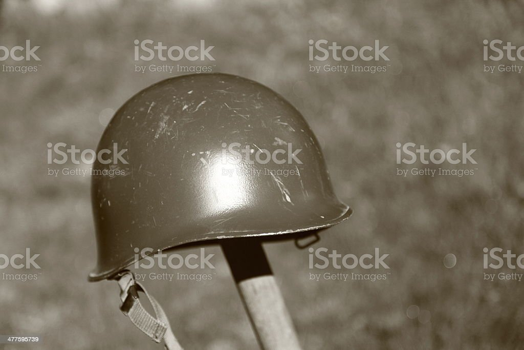 Retro NATO or US Army helmet put on spade royalty-free stock photo