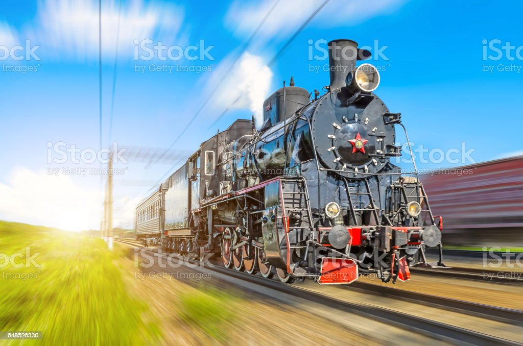 Retro old steam locomotive rushes at speed with a passenger train stock photo