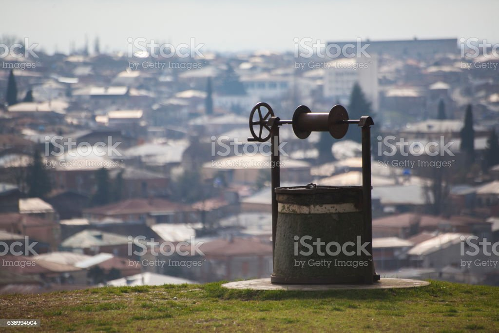 retro old well on the background of the city panorama. stock photo