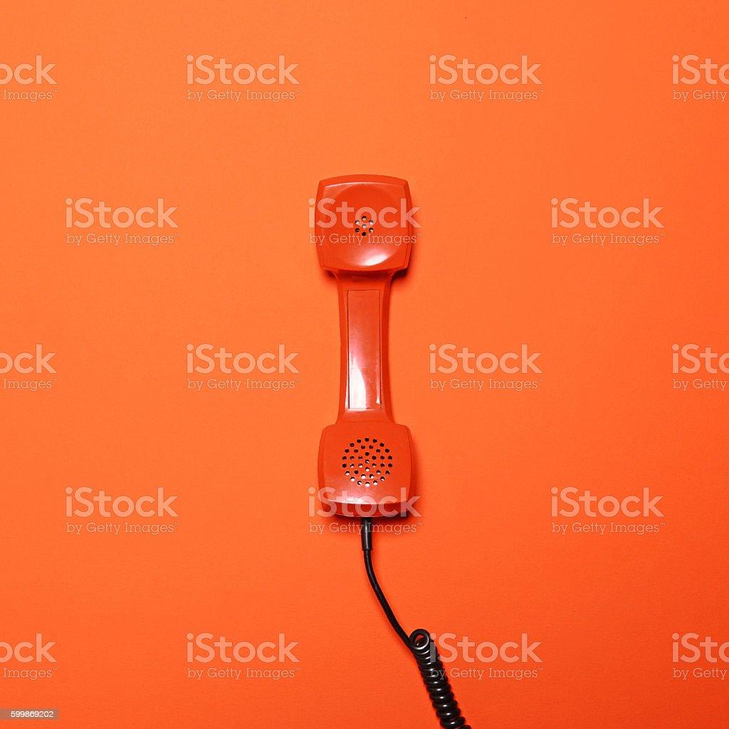 Retro orange telephone tube on orange background - Flat lay stock photo