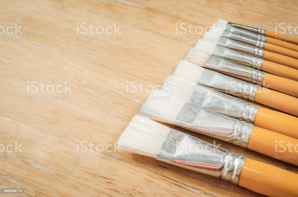 Retro paintbrushes on wooden table background with space for text stock photo