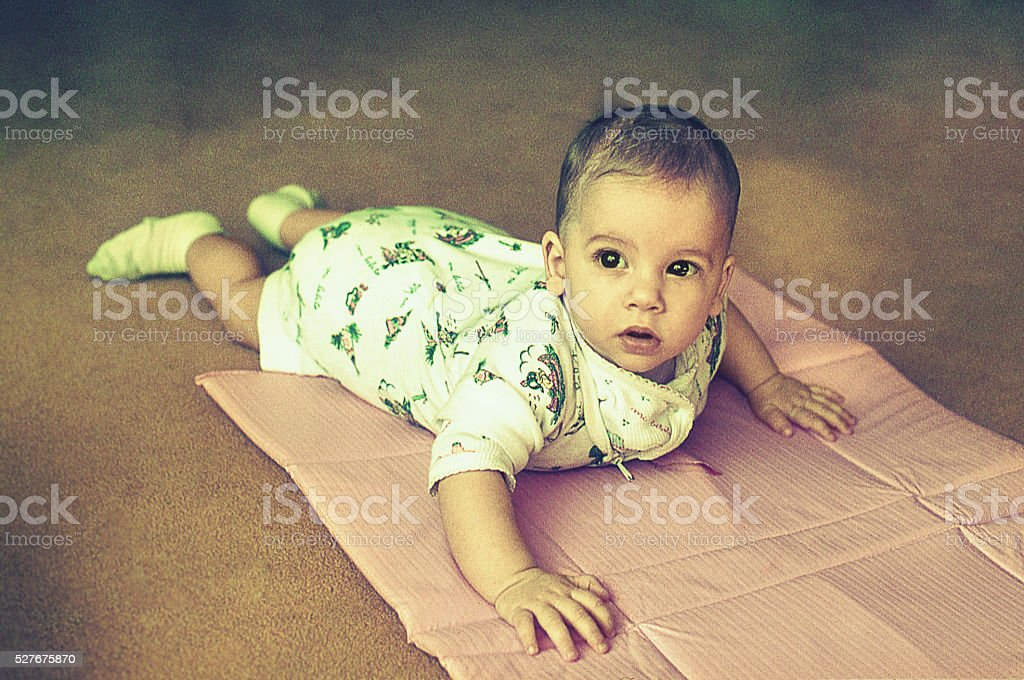 Retro photo of a baby girl on the floor stock photo