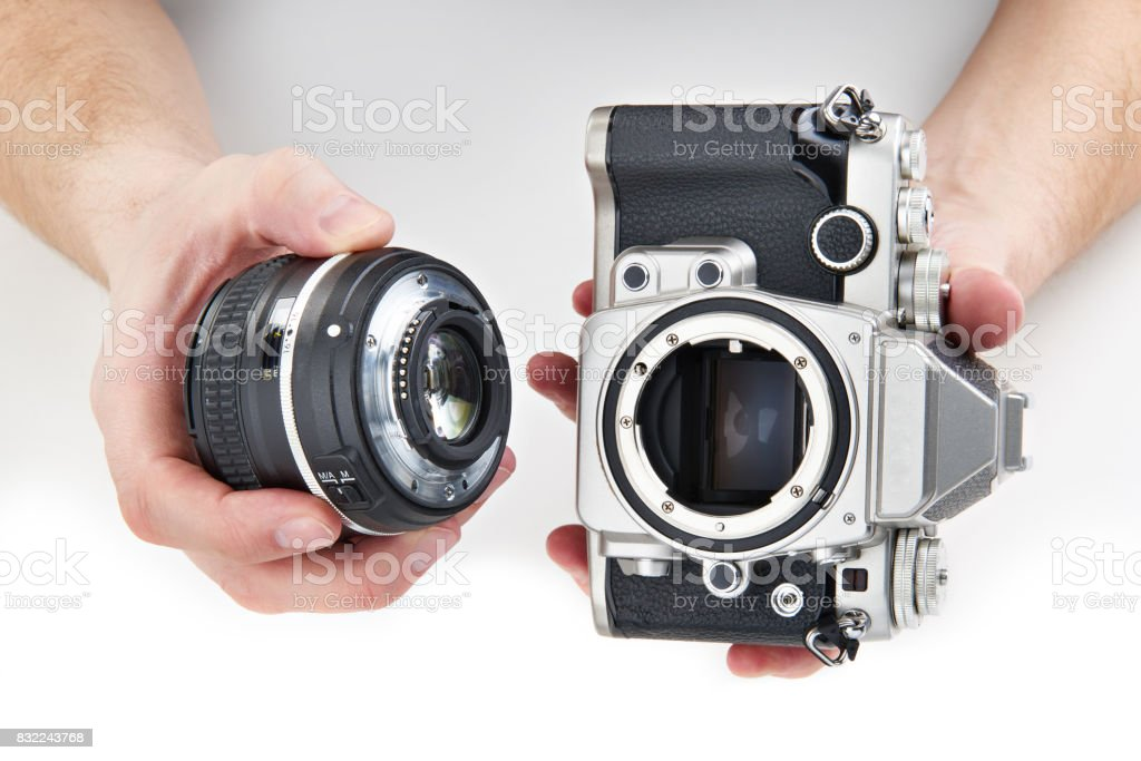 Retro photo SLR camera and lens in hands isolated stock photo