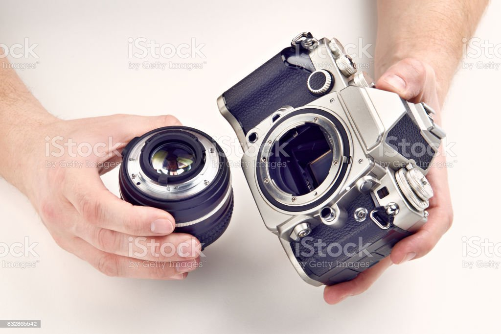 Retro photo SLR camera and lens in hands stock photo