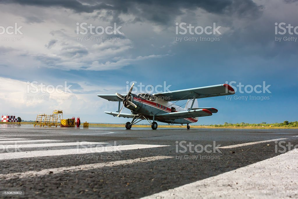 Retro plane on the airport apron after the rain stock photo