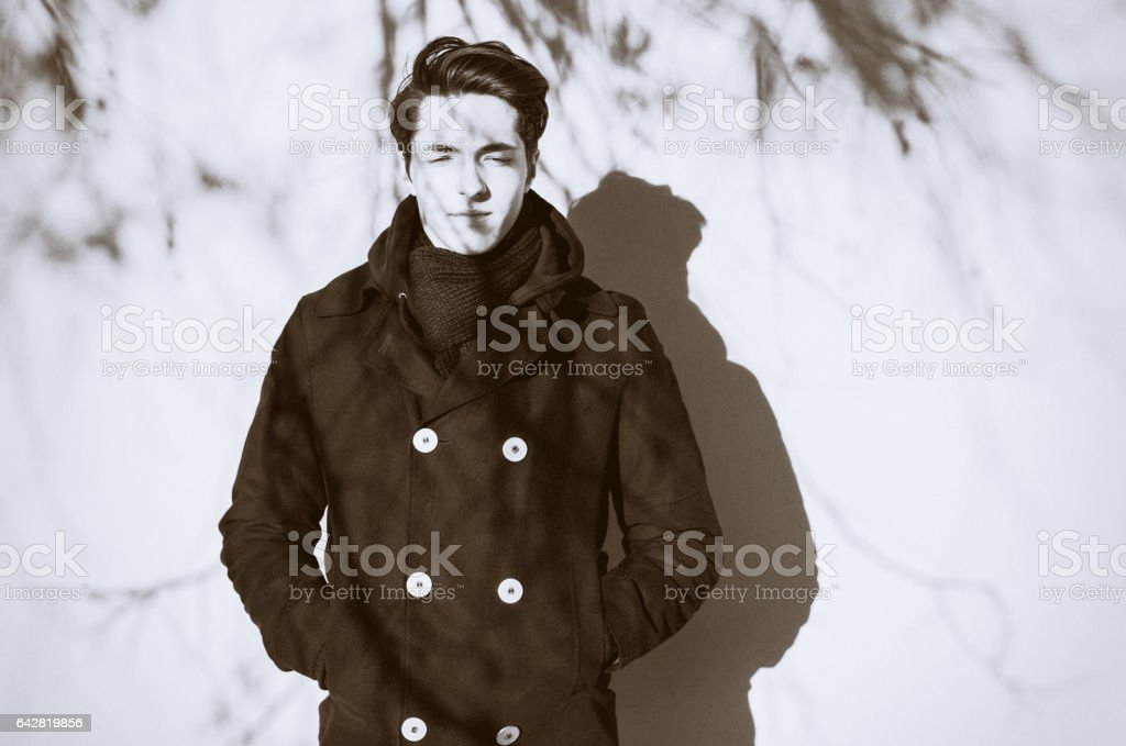 Retro portrait of a thoughtful hipster guy in front of white wall stock photo