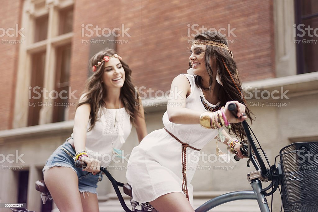 Retro portrait of two friends riding tandem bicycle stock photo