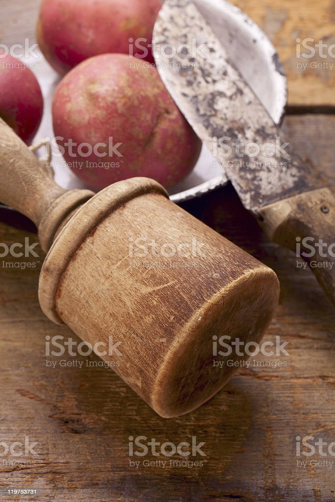 retro potato masher and knife on old wooden table royalty-free stock photo