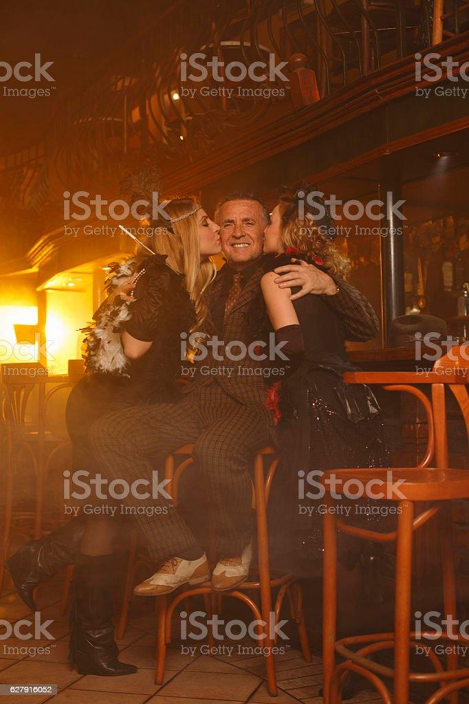 Retro pub celebration Senior man and  two young woman kiss stock photo