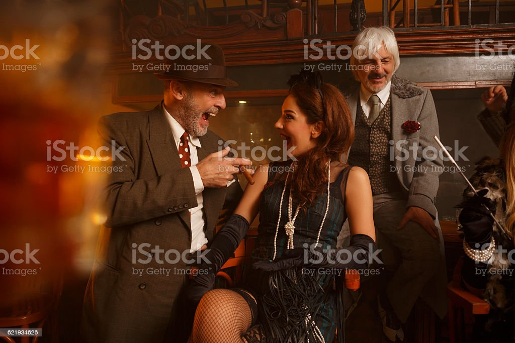 Retro pub  Old-fashioned senior men and young woman Best friends stock photo