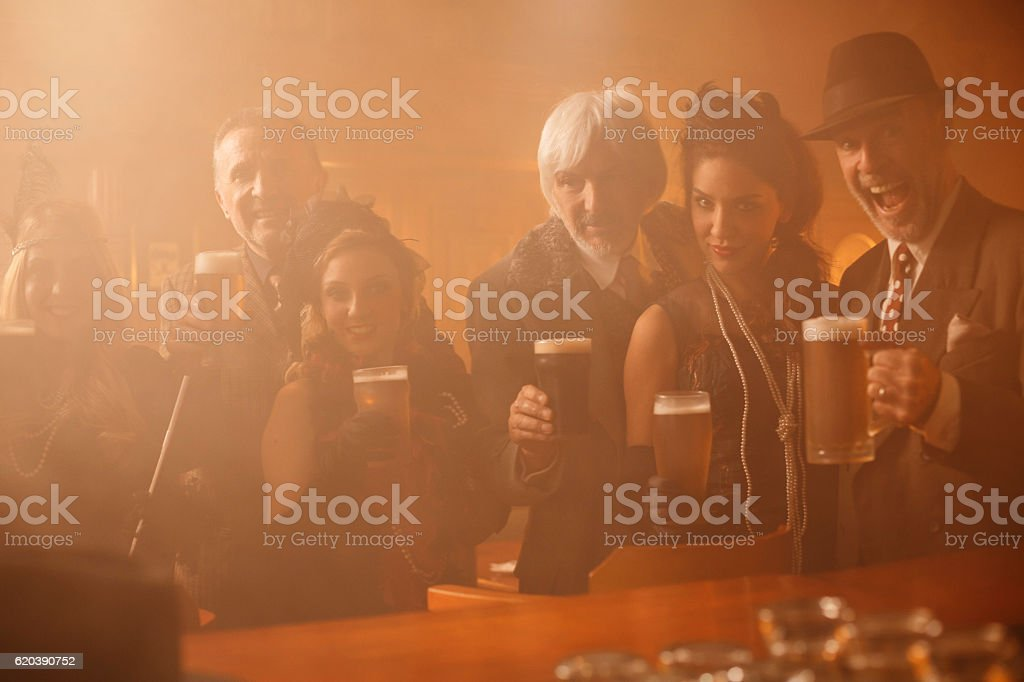Retro pub  Old-fashioned senior men and young woman drinking beer stock photo