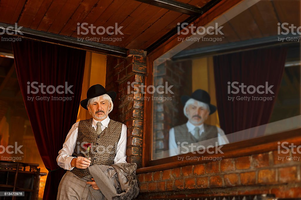 Retro romantic Old fashioned senior man in front of restaurant stock photo