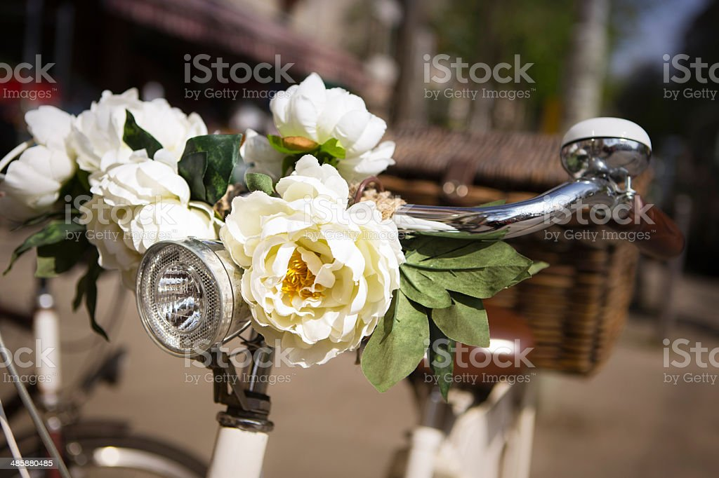 Retro style bicycle with artificial flowers on the handle bar royalty-free stock photo