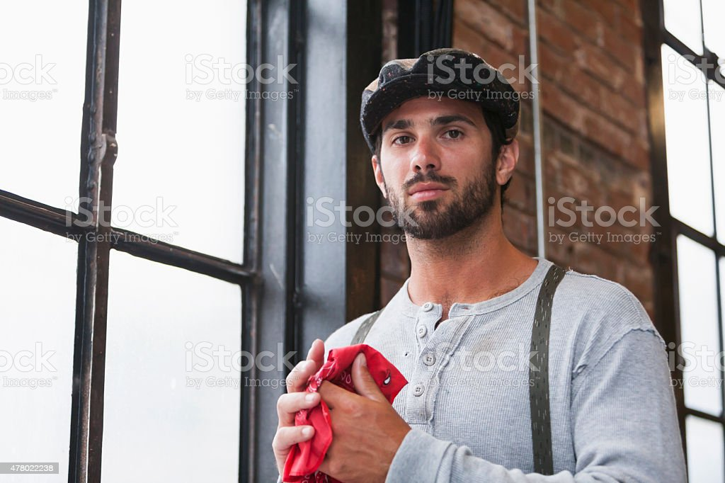 Retro style man wearing suspenders and cap by window stock photo