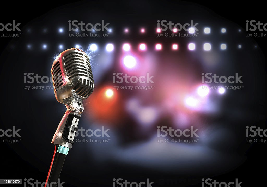 A retro style microphone with a blurred lights background stock photo