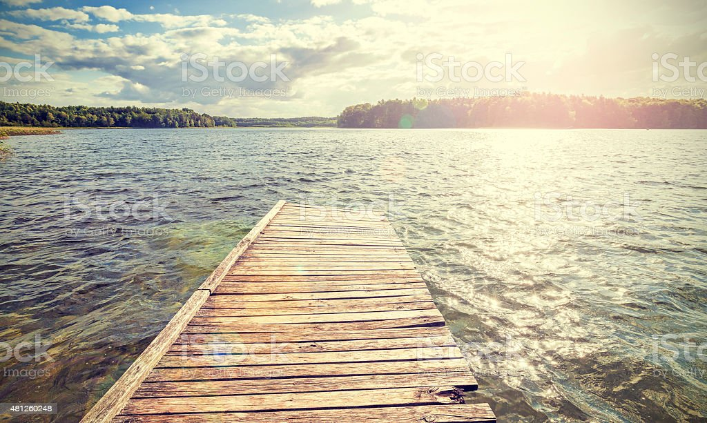 Retro style old wooden pier with flare effect at sunset. stock photo