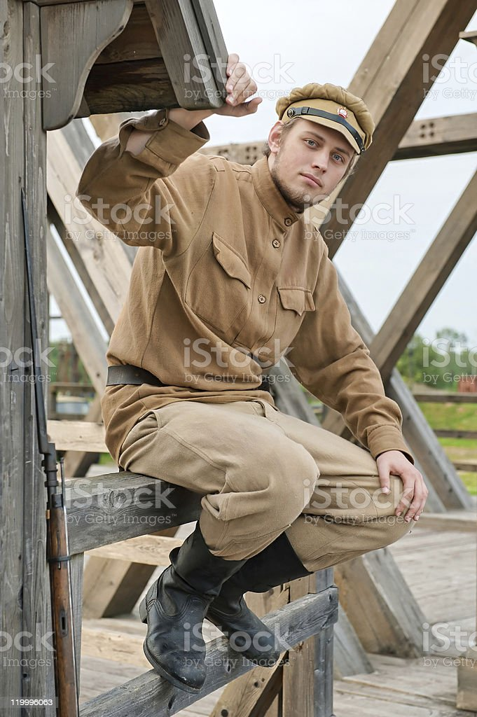 Retro style picture with soldier sitting next to the sentry. royalty-free stock photo