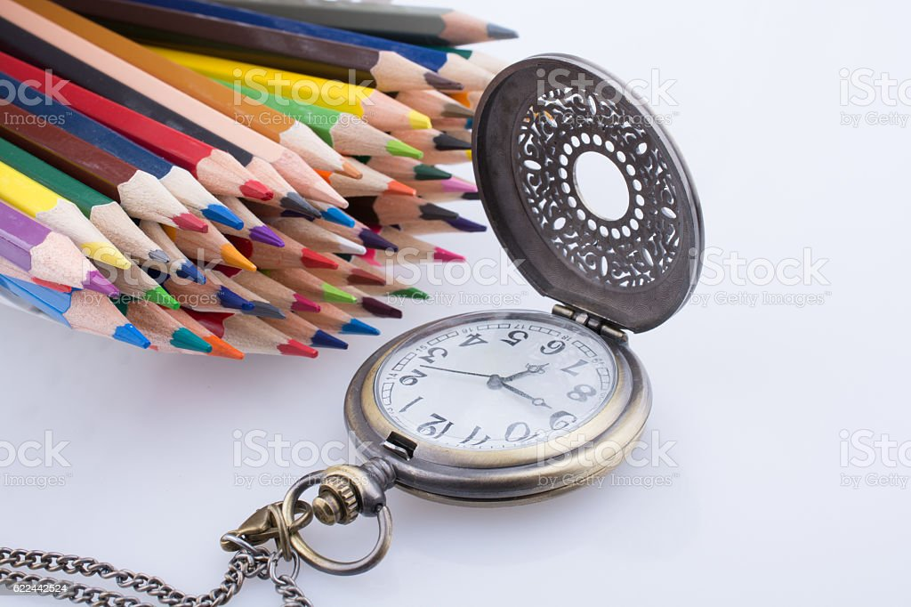Retro style pocket watch and color pencils stock photo