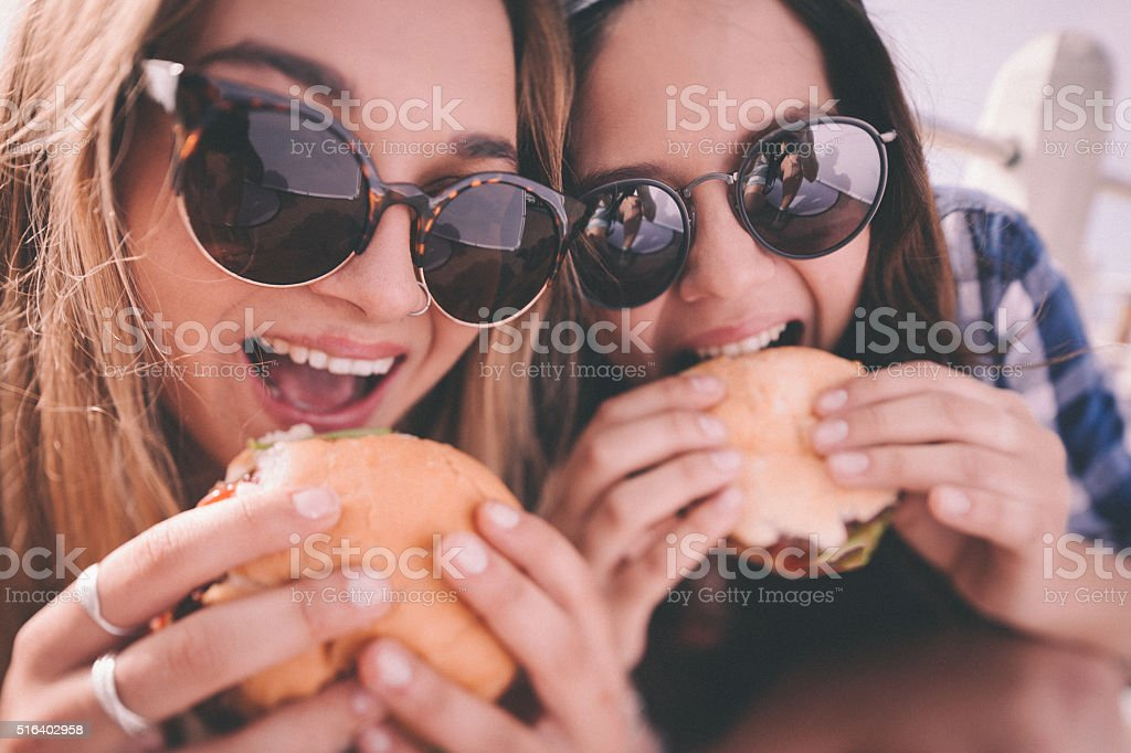 Retro style shot of teenage girl best friends eating burgers stock photo