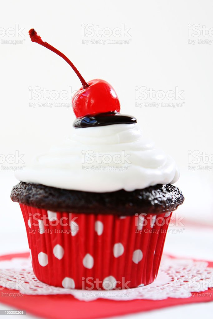 A retro styled chocolate cupcake with white icing and cherry stock photo