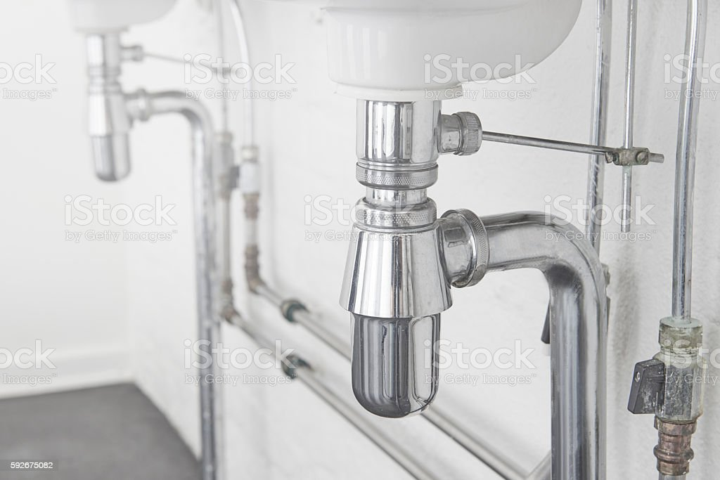 Retro styled sparse bathroom with sinks and visible tubes stock photo